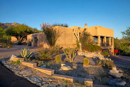 Contemporary adobe home with desert landscaping near sunset with mountain backdrop in Tucson, AZ. Stockfoto