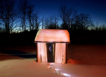 A rustic old outhouse in a field of snow with footsteps leading to it. Blue twilight sky beyond. Stock Photo - 8926402