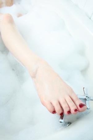 水道の蛇口のつま先で塗られた赤爪 comingo 泡風呂の外で、女性の足のクローズ アップ。