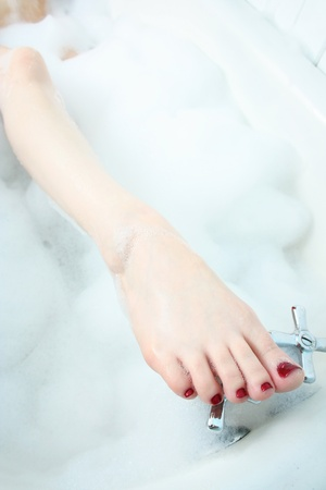Close up of a womans foot with painted red toenails comingo out of a bubble bath, with toes placed on the faucet.