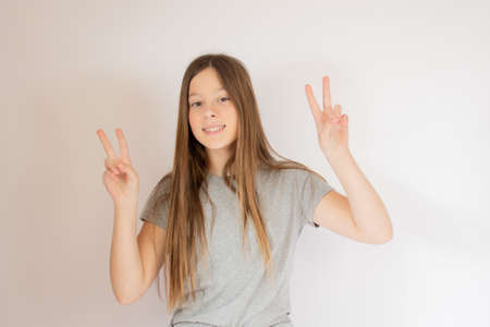 Young girl smiling with victory gestures 版權商用圖片
