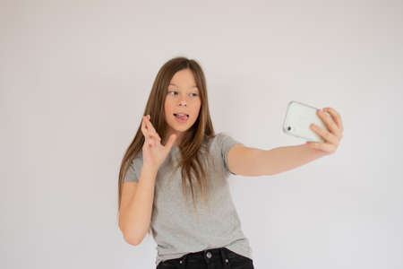 Smiling girl crossing fingers and taking a picture 版權商用圖片