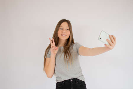 Smiling girl making a victory gesture with her finger and taking a picture