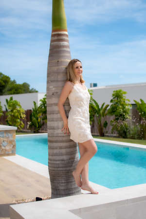 Smiling pretty woman in a nice luxury house leaning against a palm tree