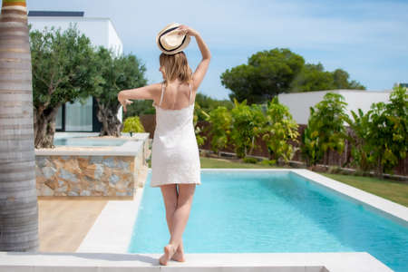 Pretty woman in a dress outside the pool