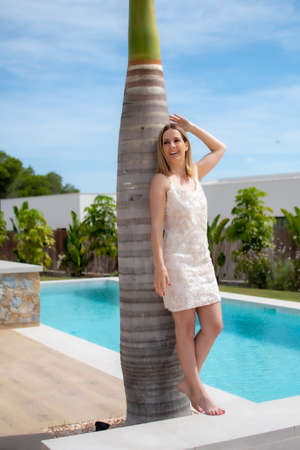 Beautiful woman leaning against a palm tree in a luxury house