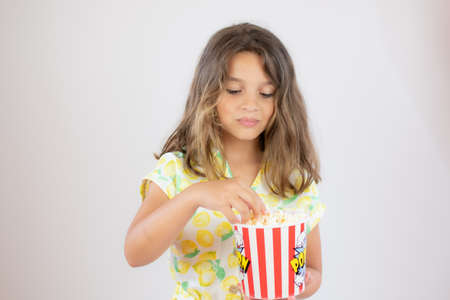 Portrait of a pretty girl with yellow shirt with popcorn in hand