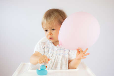 Blond baby playing with a balloon