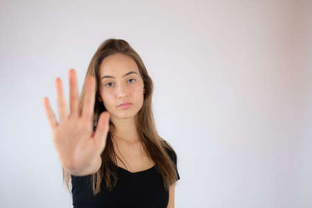Pretty young girl making stop hand gesture
