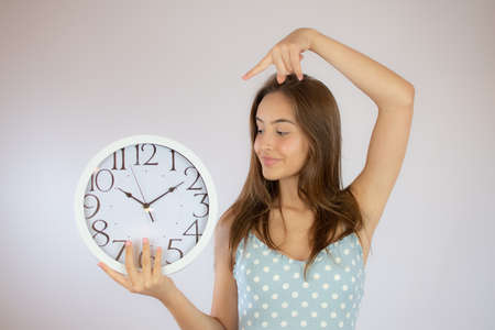 Pretty young girl in dress looking at a big clock