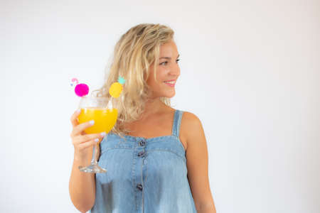 Pretty blonde woman in blue dress smiling with a fruit cocktail