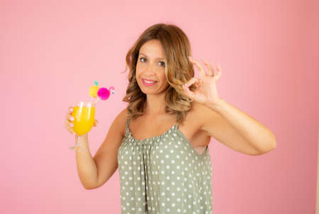 Woman with a cocktail on pink background Standard-Bild