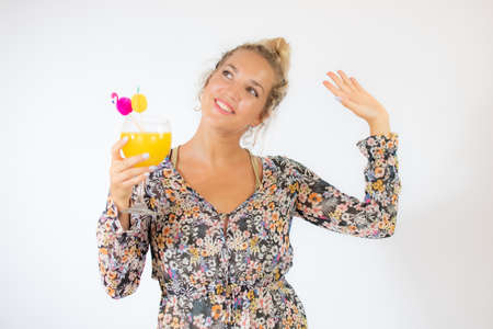 Pretty blonde woman in a flowery dress with a cocktail on white background Standard-Bild