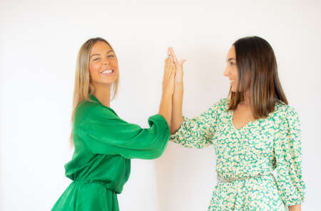 Two friends in green dresses smiling on white background Stock Photo