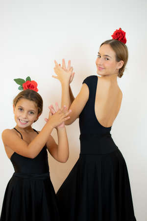 Teacher of the ballet school helps young ballerina perform different choreographic exercises. They rehearse in the ballet class. The teacher communicates with the little girl.