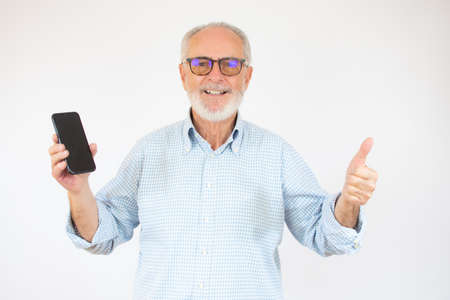 Senior man showing smartphone screen over isolated background happy with big smile doing okay sign, thumb up with fingers, excellent sign