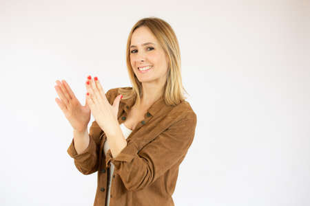 Young woman over isolated white background applauding after presentation in a conference