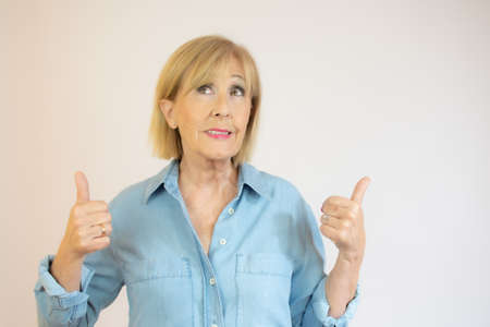 Middle age woman wearing casual denim shirt standing over isolated white background success sign doing positive gesture with hand, thumbs up smiling and happy. Cheerful expression and winner gesture. Imagens