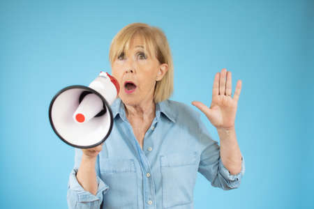 Cheerful senior woman shouting into a megaphone, communication and advertising concept