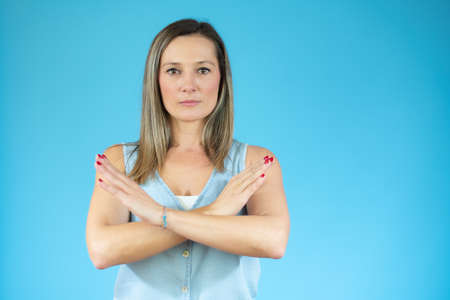 Portrait of a beautiful woman showing stop sign with palms isolated on a blue background