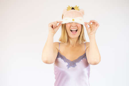 Gorgeous woman in mallow pajama posing on white background. Young lady in sleep mask playfully smiling.