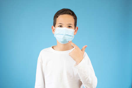 young ten years old boy in medical mask, concept of quarantine and protection from polluted air 스톡 콘텐츠