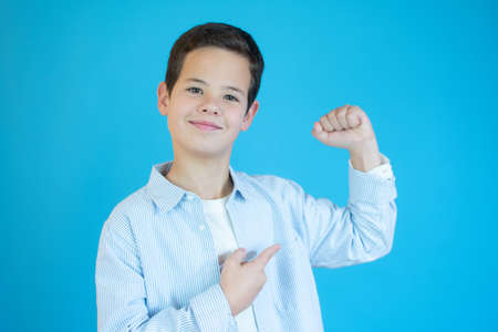 Strong boy showing muscles, isolated on blue background