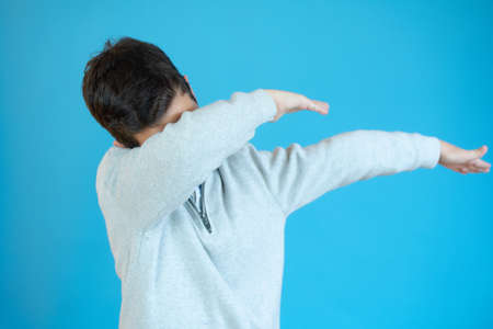 Cheerful little sportive boy child doing dab dance move, gesture while posing, standing isolated over blue background. Health and strength concept.
