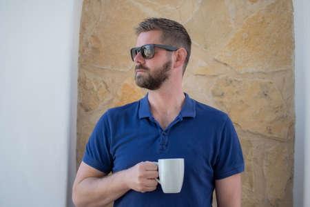 Portrait of young man in polo shirt and sunglasses drinking coffee outdoors