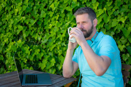 Young man sitting outdoors using laptop computer and drinking coffee.