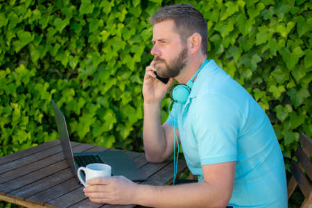 Young man sitting outdoors using laptop computer talking by mobile phone.