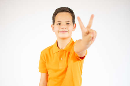 Young little boy victory gesture standing over isolate background