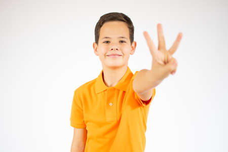 Young little boy kid wearing casual orange t-shirt standing over isolated background showing and pointing up with fingers number three while smiling confident and happy.