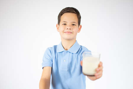 ute boy in blue shirt holding glass of milk on white background