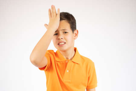 Young caucasian boy posing isolated forgetting something, slapping forehead with palm and open eyes.
