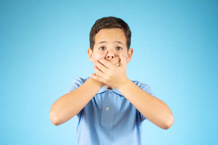 I do not see, do not speak, can not hear anything - portrait of young caucasian boy. Funny 10 year old. Handsome child in suit isolated on blue background.