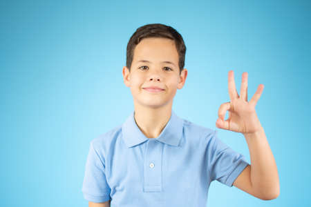 Young little boy kid wearing casual orange t-shirt standing over isolated background showing and pointing up with fingers number three while smiling confident and happy over blue background