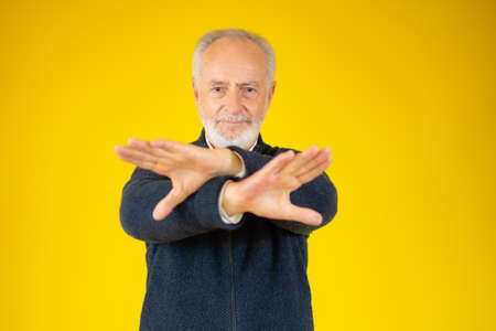 Grey bearded hair senior over yellow background Rejection expression crossing arms and palms doing negative sign
