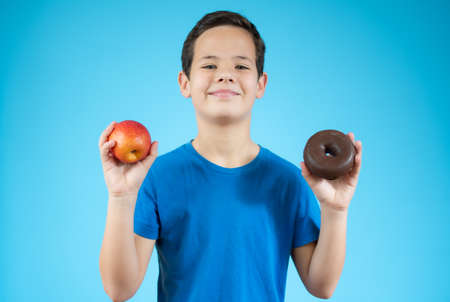 Young boy choosing between an apple and donuts isolated over blue background