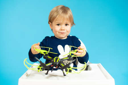 Baby boy sitting and holding a drone isolated over blue background.