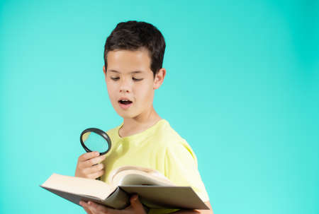 Young boy looking through a magnifying glass while reading an open book, isolated on green background