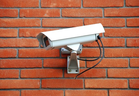 building security: Security cam on red brick wall Stock Photo