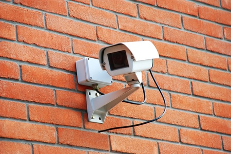Security cam on red brick wall photo