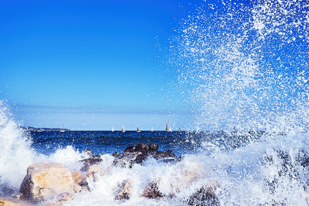 Sea view. Sailing regatta. Seacoast, stones on the shore. Big wave with foam and spray
