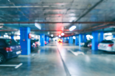 Blurred spacious underground parking for car buyers in a large modern shopping mall. Bright abstract background ideal for any desig