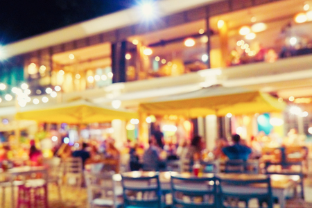 Blurred and bokeh restaurant. Blurred bright restaurant on the beach in hot summer. Happy company of friends in a restaurant at a big table at the birth. Bright holiday lights 스톡 콘텐츠