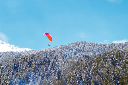 Landscape of mountains against the blue sky and white clouds. Forest of pine trees. Paratrooper flying over the mountain massif against the blue sky 스톡 콘텐츠