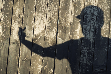 The shadow of a man on wooden boards. Raised hand in greeting shows provocation indecent gesture fuck