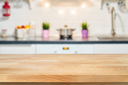 A wooden table top of the kitchen table on a blurry background of the kitchen interior. Bright interior decoration of home cooking. Bright ready-made picture for your individual design