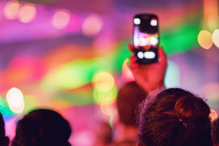 Blurred silhouette of a girl shooting a concert on a smartphone. Youth Music Festival of pop music. Laser show on the stage. The crowd of fans. Blurred bokeh basic background for design